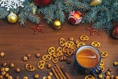 葡萄酒杯热的茶用在用杉木装饰的木背景的薄脆饼干 图库摄影
