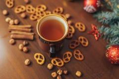 葡萄酒杯热的茶用在用杉木装饰的木背景的薄脆饼干 免版税图库摄影