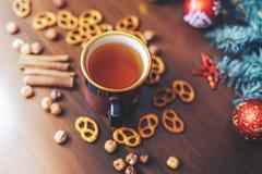 葡萄酒杯热的茶用在装饰的木背景的薄脆饼干 免版税库存图片
