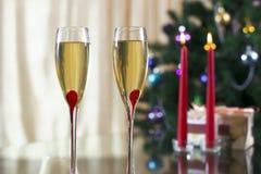 葡萄酒杯用香槟、圣诞节云杉、礼物和蜡烛 免版税图库摄影