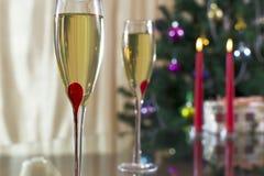 葡萄酒杯用香槟、圣诞节云杉、礼物和蜡烛 免版税库存照片