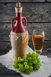 葡萄酒杯白葡萄酒、在木背景的瓶酒和葡萄 免版税库存照片