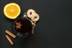 葡萄酒杯被仔细考虑的酒用曲奇饼和桔子在黑台式视图 免版税库存照片