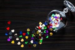 从葡萄酒杯驱散的明亮五彩纸屑心形 免版税库存图片