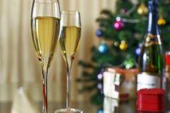 葡萄酒杯,瓶香槟、圣诞树和礼物 免版税库存图片