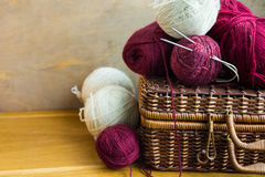 葡萄酒柳条筐红色白色毛纱球线团,在木桌上的针,编织,工艺,爱好概念 库存照片