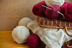 葡萄酒柳条筐红色白色毛纱,片断在木桌上的被编织的针线,编织,工艺,爱好conce球线团  免版税库存照片