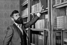 葡萄酒样式和时尚 昂贵的衣服的有胡子的人在他的内阁 教授在大图书馆里站立并且拿着书 免版税库存照片