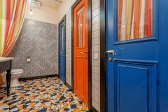 葡萄酒样式有老木门的洗手间室内部对卫生间 在五颜六色的地垫的蓝色和红色门 免版税库存图片