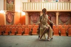 葡萄酒样式的女孩在一件减速火箭的礼服坐一个空的剧院的阶段 在背景中,空的观众席 库存图片
