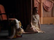 葡萄酒样式的女孩在减速火箭的礼服坐一个空的剧院的阶段 免版税库存照片