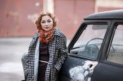 葡萄酒样式的红发女孩在老汽车附近 库存图片