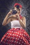 葡萄酒样式-使用一台老照相机的妇女在圆点穿衣 库存图片