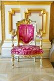 葡萄酒桃红色丝绸和金框架椅子 库存图片