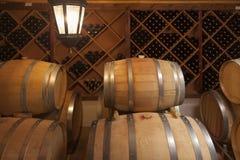 葡萄酒桶和瓶在地窖里 库存照片