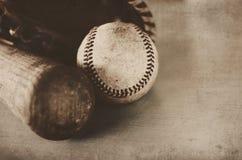 葡萄酒棒球棒和老球,与皮手套在背景中 免版税库存图片