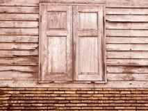 葡萄酒棕色独特的古老木窗口和老高明的砖墙减速火箭的样式在农村背景的 库存图片
