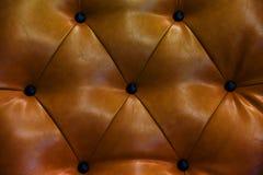 葡萄酒棕色皮革和按钮沙发 图库摄影