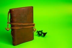 葡萄酒棕色皮革笔记本 绿色背景 免版税图库摄影
