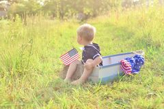 葡萄酒水手服的男孩和在小船的美国国旗在草 库存图片