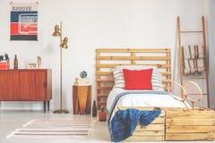 葡萄酒海报和内阁在金黄灯旁边和木床与床头柜与书和时钟 免版税库存照片