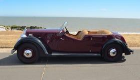 葡萄酒深红流浪者汽车在沿海岸区散步停放了 库存图片