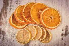 葡萄酒照片、在老木背景的切片干柠檬和桔子 库存图片