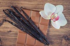 葡萄酒照片、牛奶巧克力、芬芳香草棍子和开花的兰花 免版税库存照片