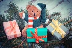 葡萄酒照片、玩具熊与五颜六色的礼物圣诞节的和云杉的分支 免版税库存图片
