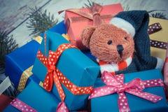 葡萄酒照片、玩具熊与五颜六色的礼物圣诞节的和云杉的分支 图库摄影