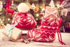 葡萄酒照片、礼物圣诞节的与羊毛袜子和盖帽在圣诞树背景与装饰 库存图片