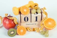 葡萄酒照片、立方体日历、果子、哑铃和卷尺,新年决议 库存照片
