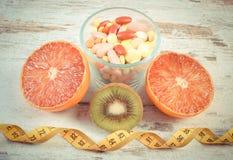 葡萄酒照片、自然果子、厘米和药片,减肥,选择在健康营养和医疗补充之间 库存照片