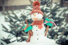 葡萄酒照片、雪人有礼物的圣诞节的或华伦泰针叶树背景的盖了雪 库存图片