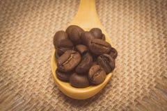 葡萄酒照片,咖啡豆堆与木匙子的在黄麻帆布 图库摄影