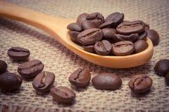 葡萄酒照片,咖啡豆堆与木匙子的在黄麻帆布 库存照片