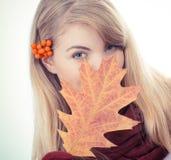 葡萄酒照片,女孩用在拿着秋季叶子的头发的花揪 免版税库存图片