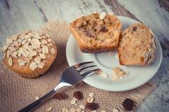葡萄酒照片,新鲜的松饼用燕麦粥烘烤了用在白色板材,可口健康点心的全麦的面粉 免版税库存照片