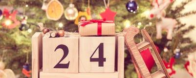葡萄酒照片,约会12月24日、被包裹的礼物和圣诞树与装饰,圣诞前夕时间概念 免版税库存照片