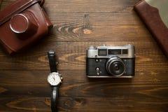 葡萄酒照相机、笔记本和手表顶视图在木backg 免版税库存照片