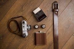 葡萄酒照相机和皮带在木地板上 免版税库存照片