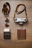 葡萄酒照相机和皮带在木地板上 免版税库存图片