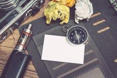 葡萄酒照相机顶视图,压皱纸、电子香烟和计划者书布局在木地板上 库存图片