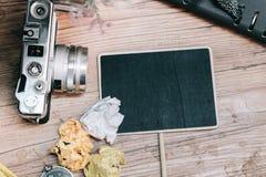 葡萄酒照相机,压皱纸、指南针和计划者在木地板上的书布局 图库摄影