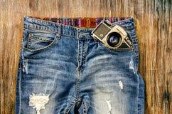 葡萄酒牛仔裤细节有经典照相机的 免版税库存图片