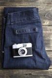 葡萄酒牛仔裤细节有经典照相机的 免版税库存照片