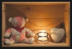 葡萄酒玩具熊、蜡烛和心形的石头在一个木箱 库存图片