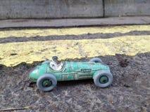 葡萄酒玩具赛车&司机接近与破旧的绿色古色,在双黄线前面禁止停车制约 免版税库存图片