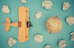 葡萄酒玩具飞机和地球在纸云彩旅行概念 免版税库存照片