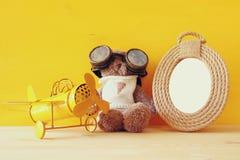 葡萄酒玩具飞机和逗人喜爱的玩具熊在空的框架旁边 库存照片